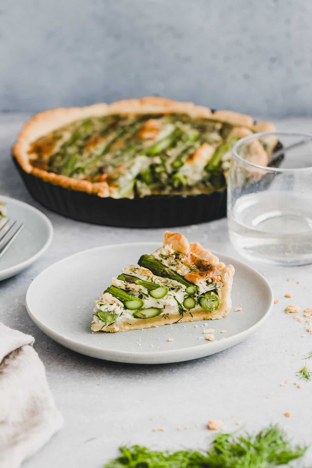 a slice of green asparagus quiche on a blue plate