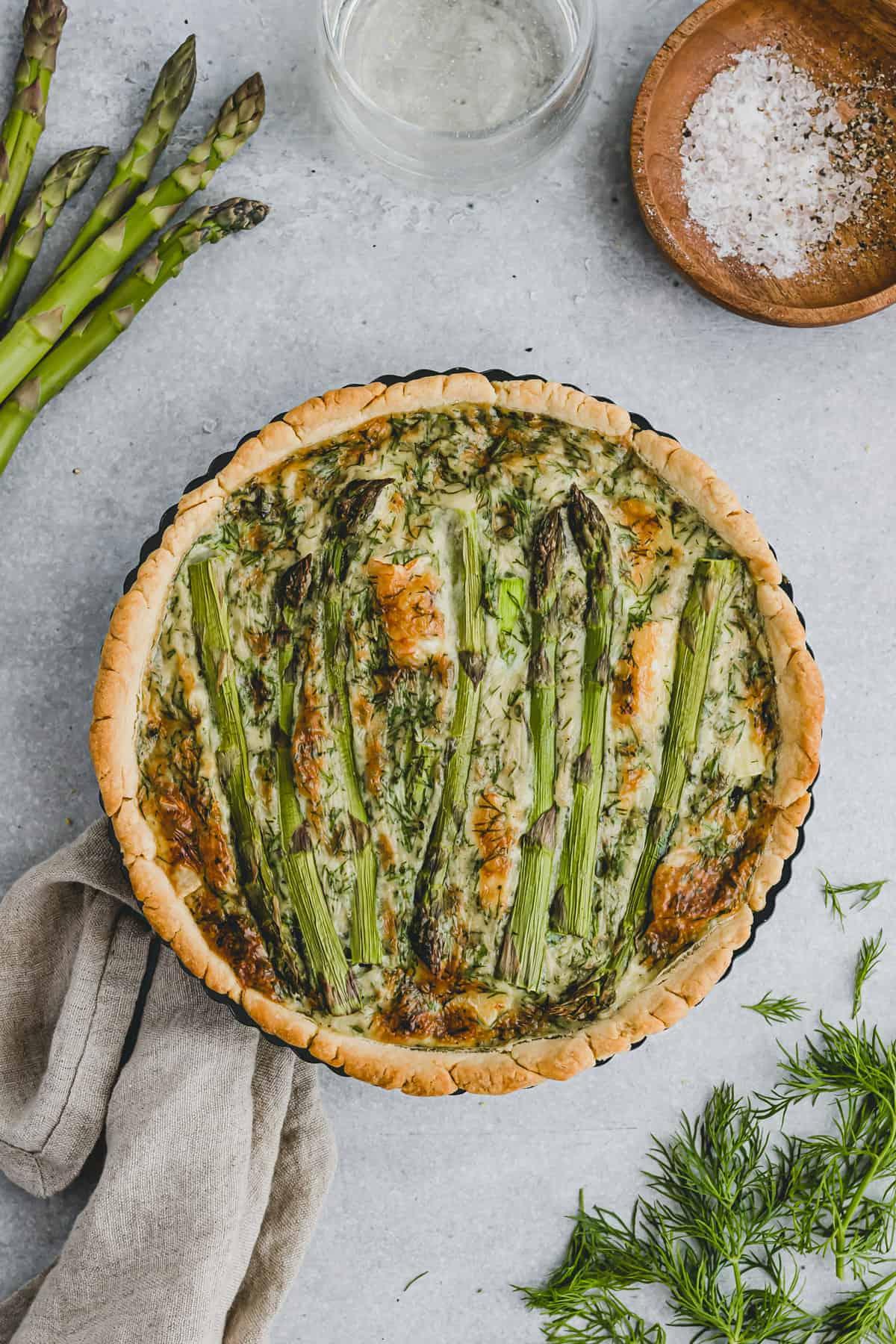 asparagus quiche in a tart pan next to green asparagus