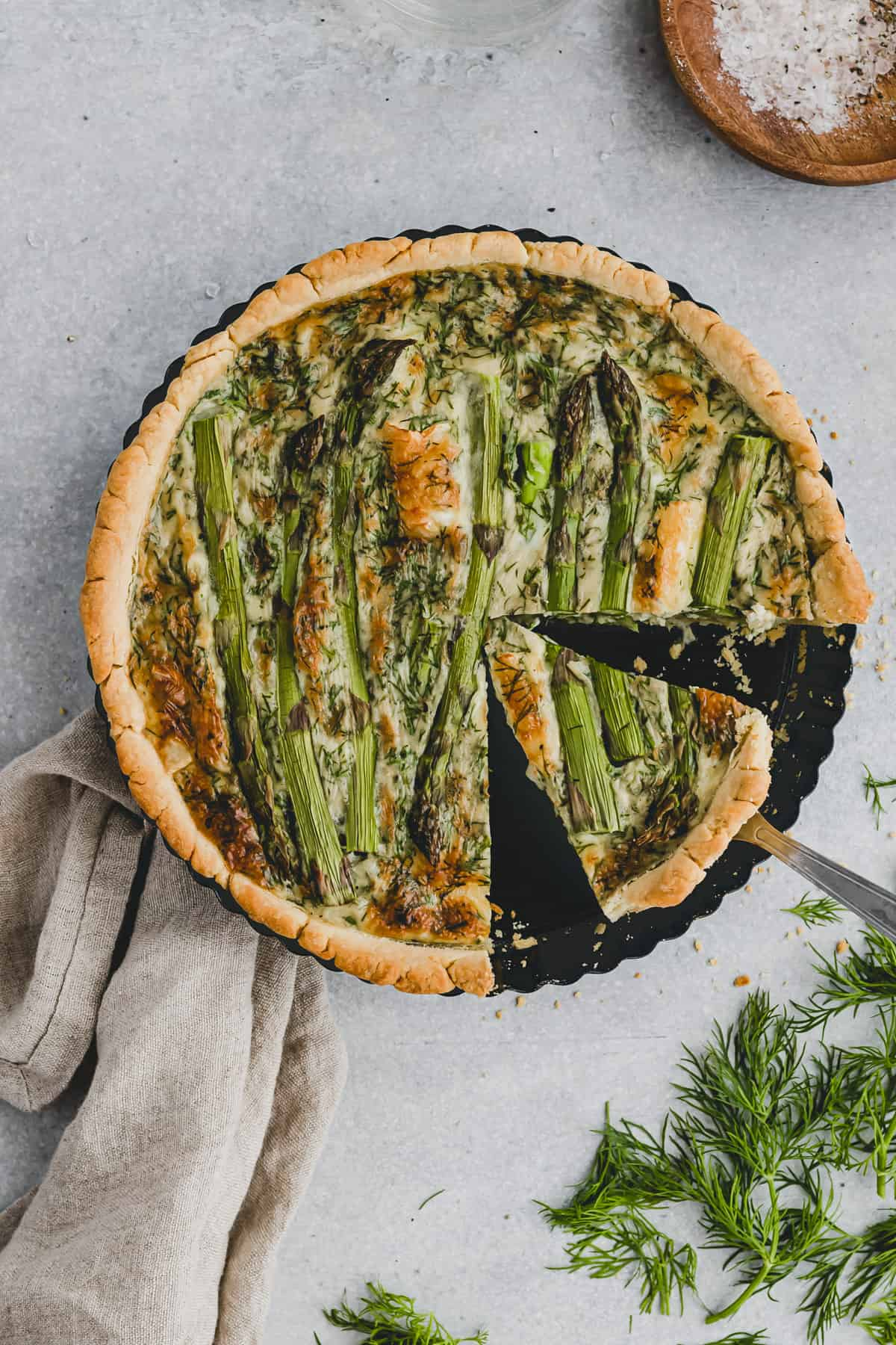 sliced quiche with green asparagus in a quiche pan