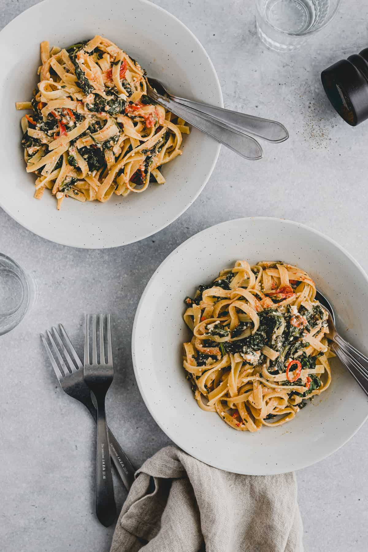 two dished with baked feta spinach pasta