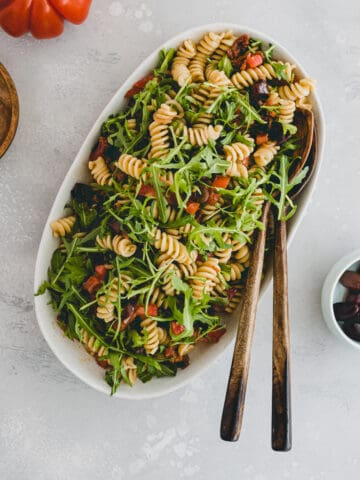 Mediterranean Pasta Salad next to a tomato and olives