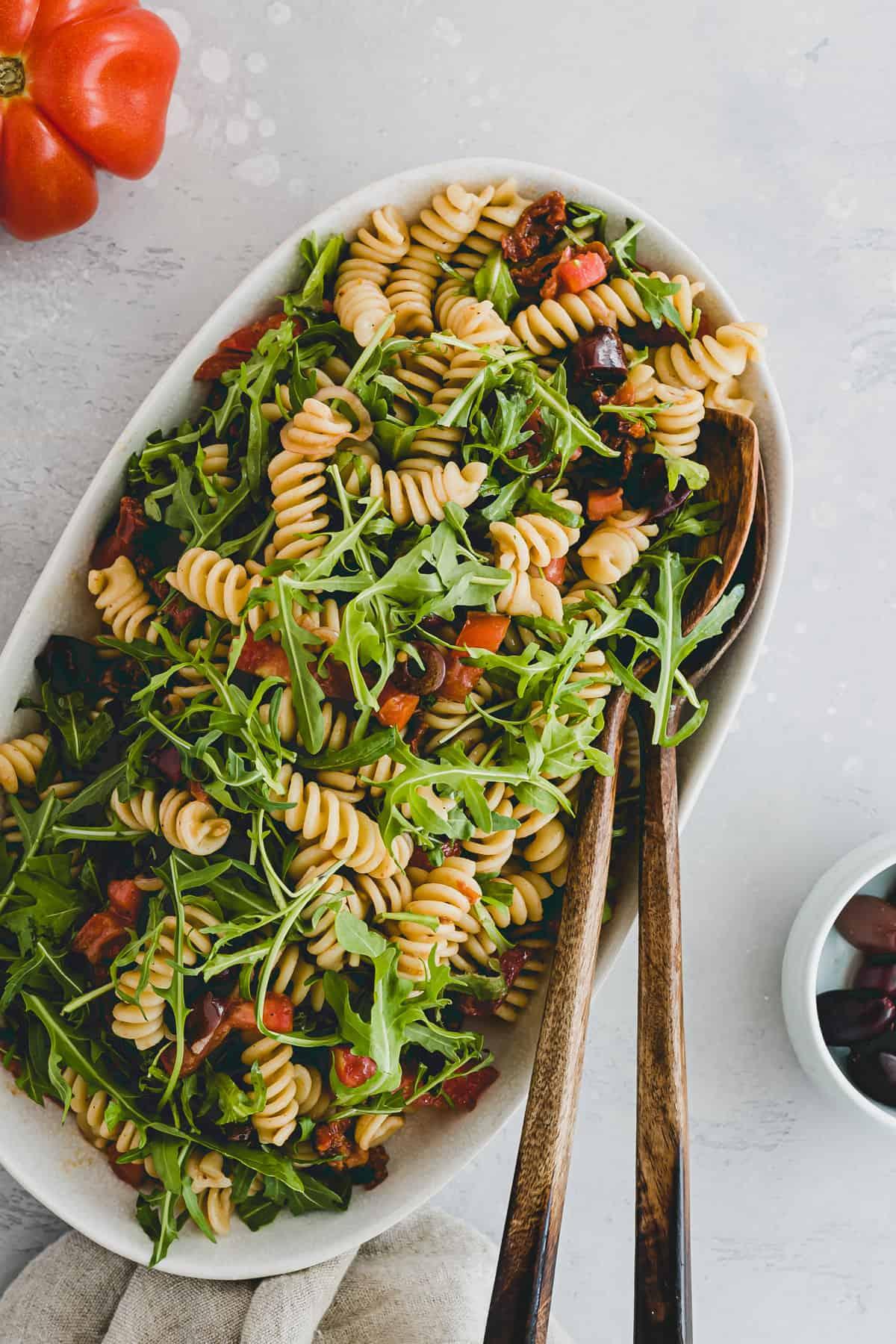 veganer nudelsalat mit rucola auf einer salatplatte