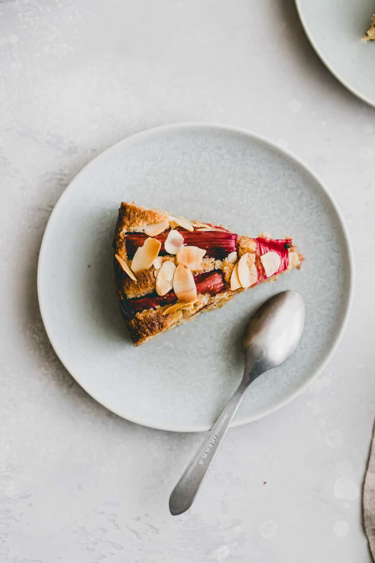 a slice of rhubarb almond cake on a blue plate