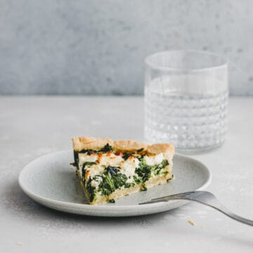 a slice of spinach and feta quiche on a blue plate