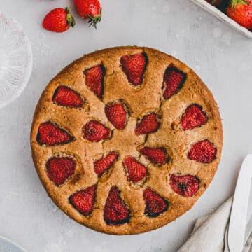 strawberry almond cake next to a few strawberries