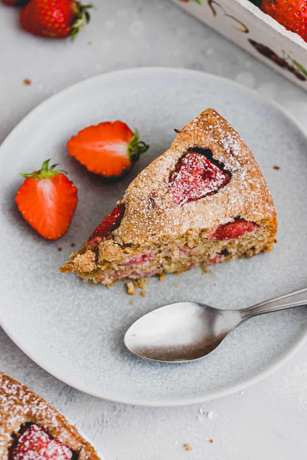 a slice strawberry almond cake on a blue plate