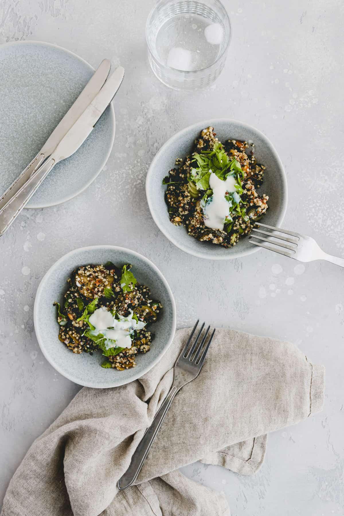 veganer quinoa salat mit joghurt und kräutern in zwei blauen schüsseln