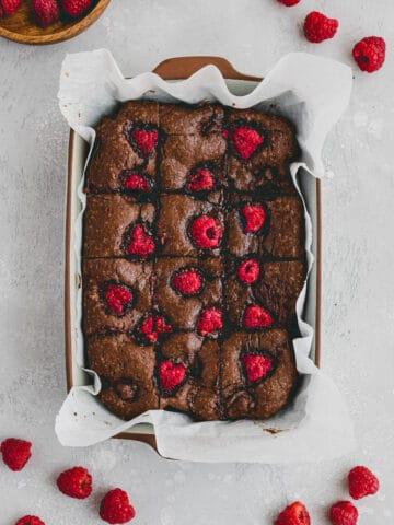 himbeer brownies in einer backform neben frischen himbeeren