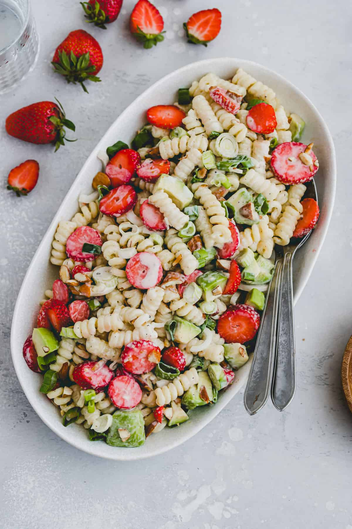 vegan cold pasta salad with strawberries and avocado on a serving platter