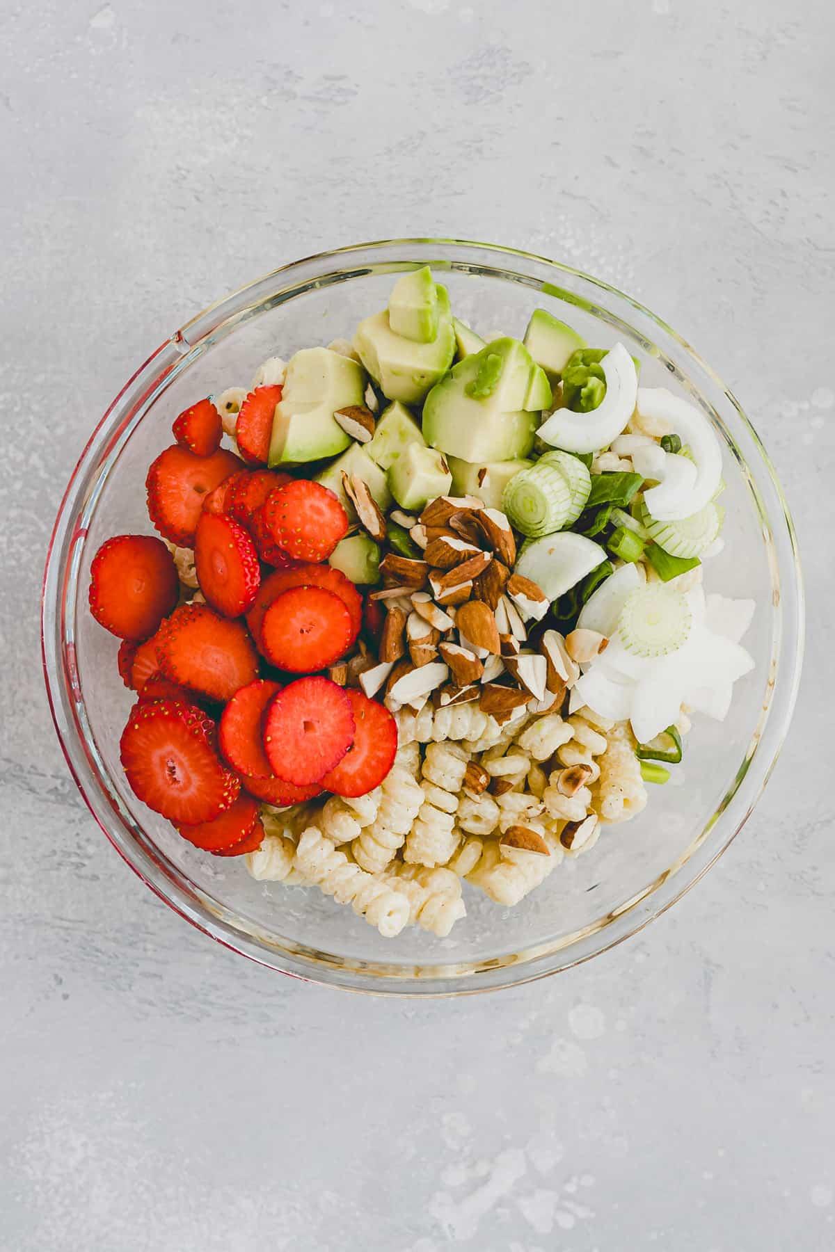 zutaten für sommerlicher nudelsalat mit erdbeeren und avocado in einer glasschüssel