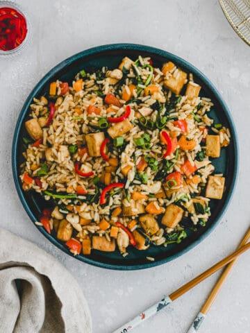gebratener reis mit gemüse und tofu auf einem blauen teller