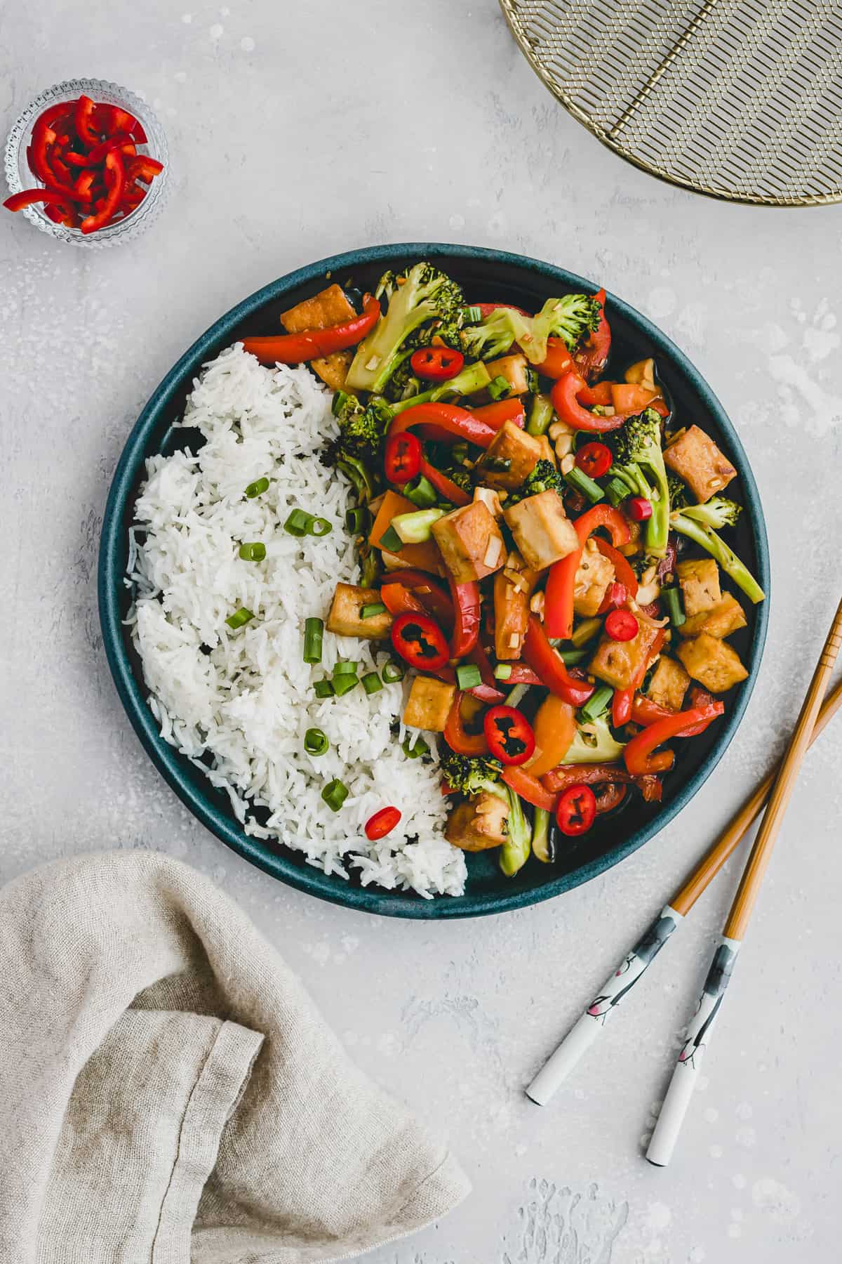 tofu stir fry on a plate next to chopsticks