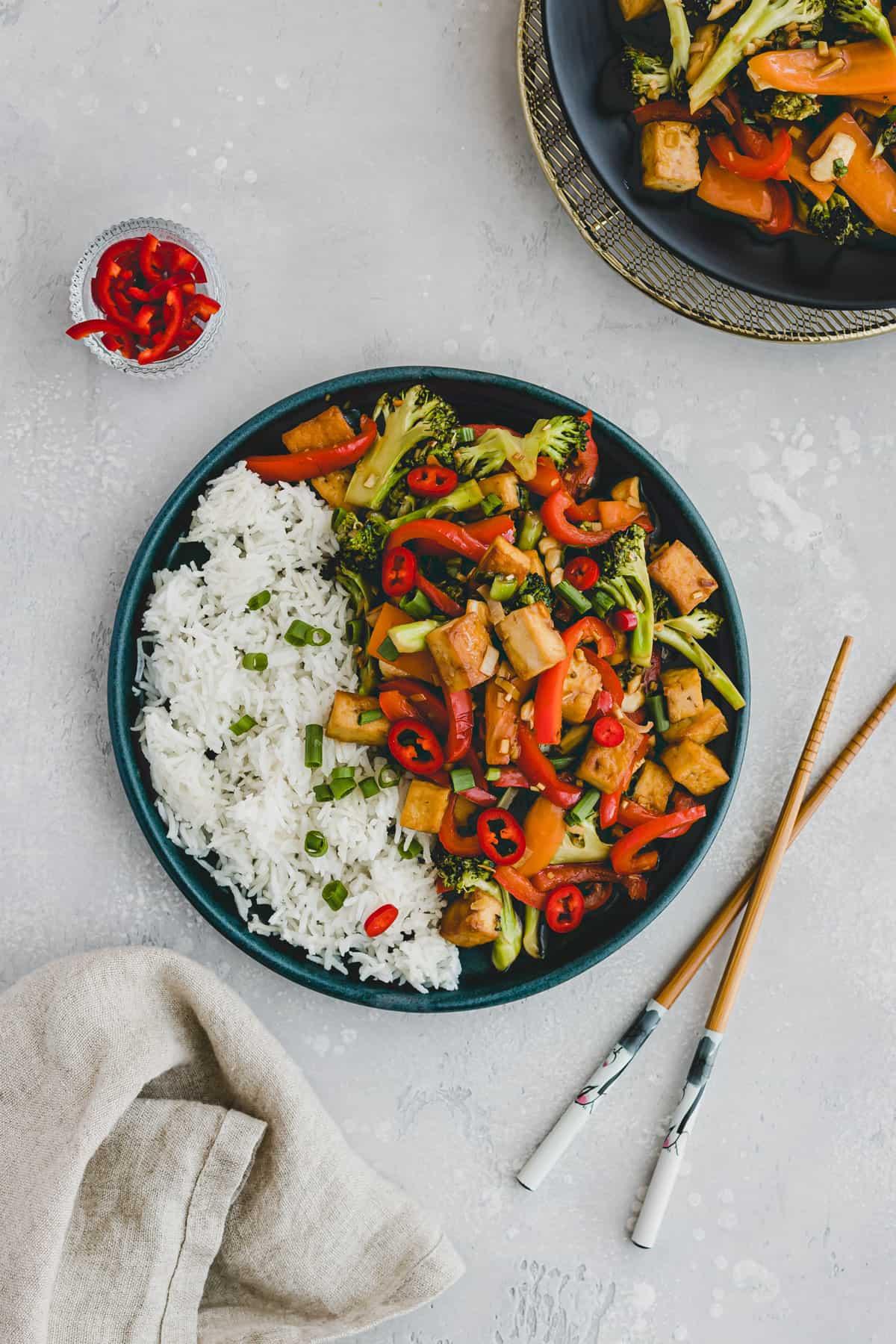 two plates of tofu vegetable stir fry
