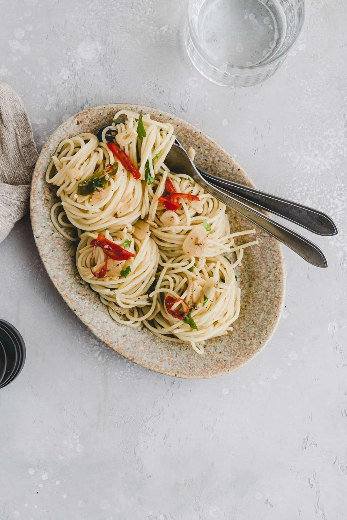 spaghetti aglio e olio on a brown plate with cutlery