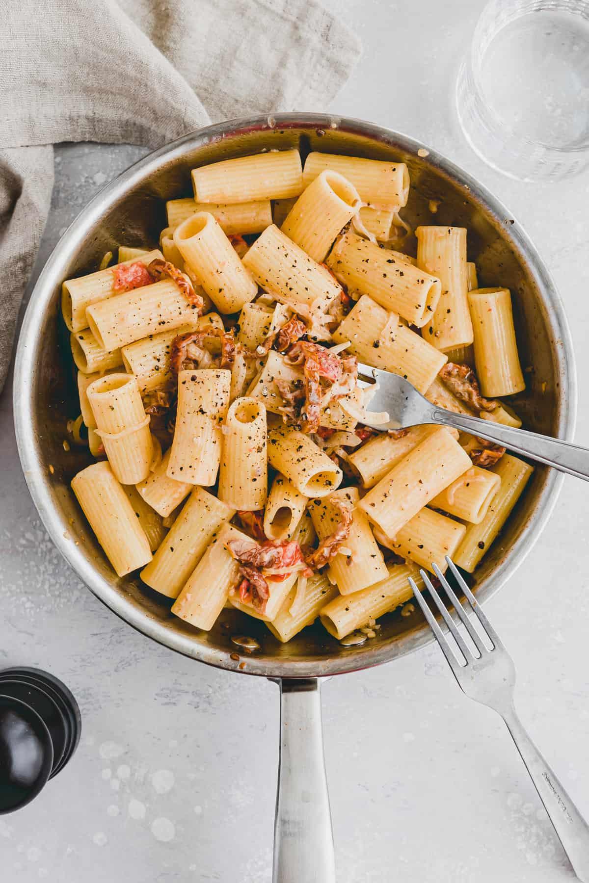 vegane pasta mit getrockneten tomaten in einer pfanne mit zwei gabeln