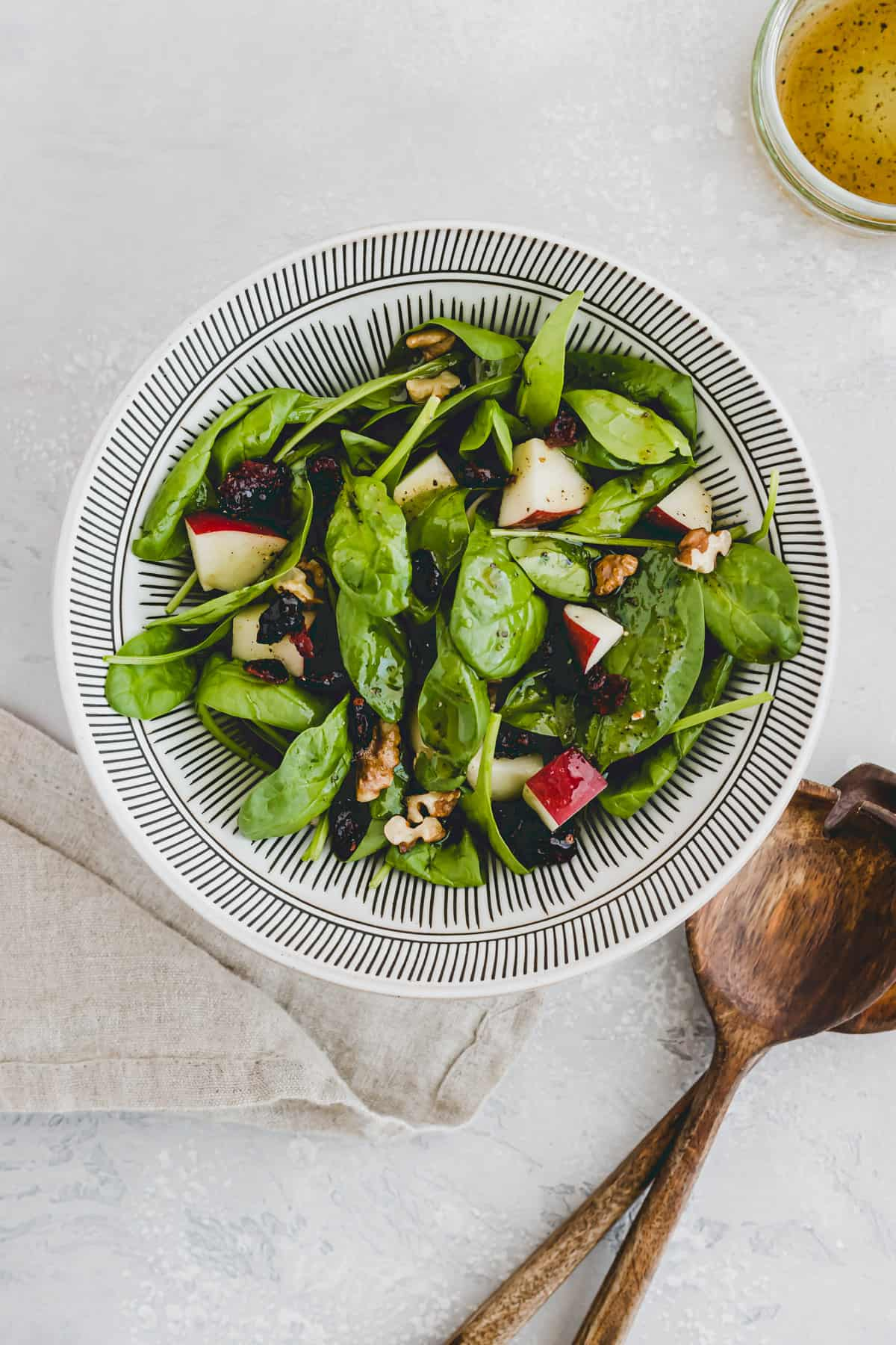 Spinach Salad with Apple, Cranberry & Walnut next to a glass vinaigrette