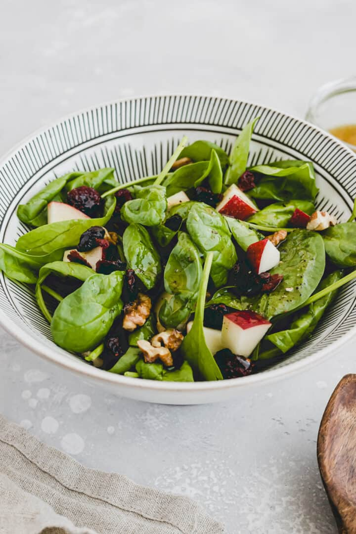 spinach cranberry salad with apple in a bowl