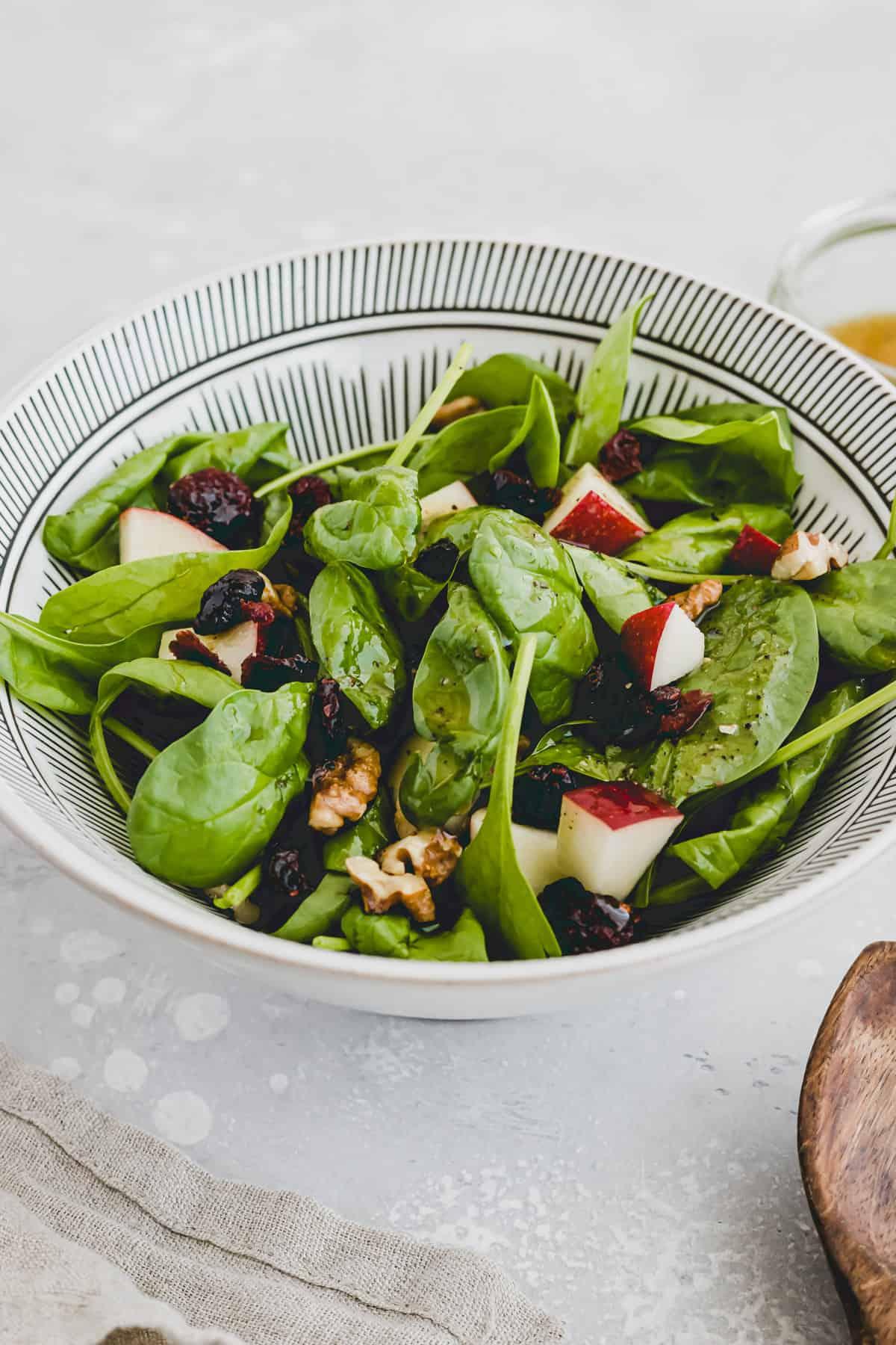 spinatsalat mit apfel, walnuss, cranberry in einer schüssel